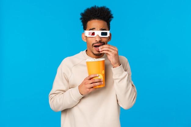 Ragazzo sciocco afroamericano spaventato e divertito, incuriosito che guarda film in 3d al cinema, impaurito di guardare lo schermo ma interessato a cosa succederà dopo, mangiando popcorn e chinandosi paura, parete blu