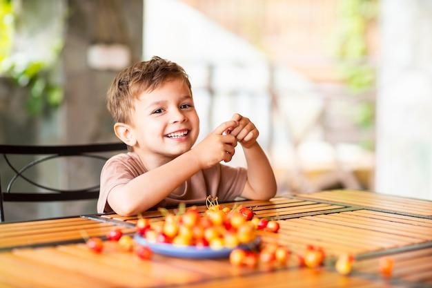 Ragazzo seduto a un tavolo di legno e tenendo le ciliegie nelle sue mani