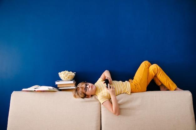 Ragazzo seduto sul divano, mangiando pop corn e giocando con il gamepad durante la sua lezione online a casa, distanza sociale durante la quarantena, autoisolamento, concetto di educazione online