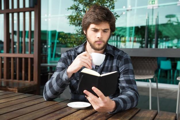 Ragazzo serio eccitato con una interessante storia di libri