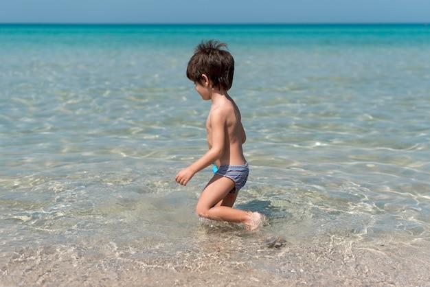 Ragazzo sideview in spiaggia a giocare in acqua