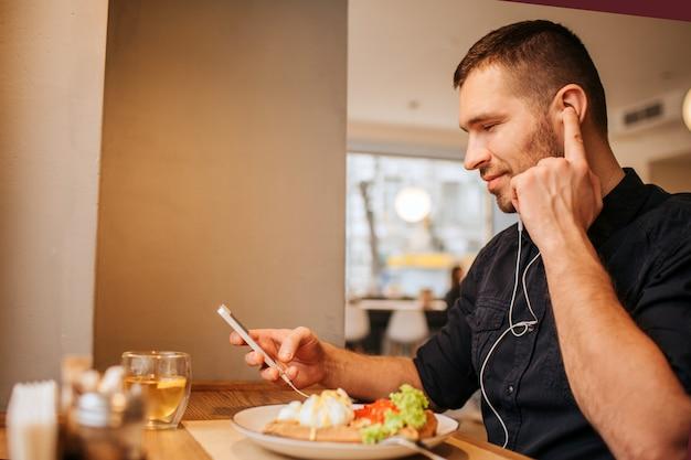 Ragazzo simpatico e attraente è seduto al tavolo e con il telefono in mano. sta ascoltando musica tramite le cuffie. guy tiene l'indice vicino all'orecchio e guarda il telefono.