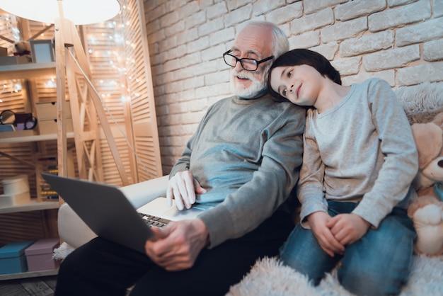 Ragazzo sonnolento che si siede vicino al nonno funzionante del computer portatile