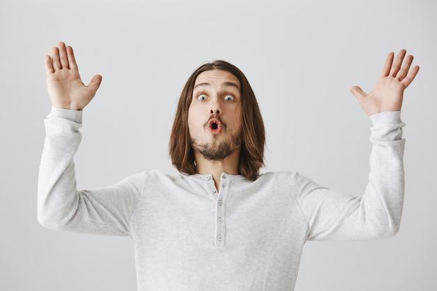 Ragazzo sorpreso che alza le mani, guardando sbalordito