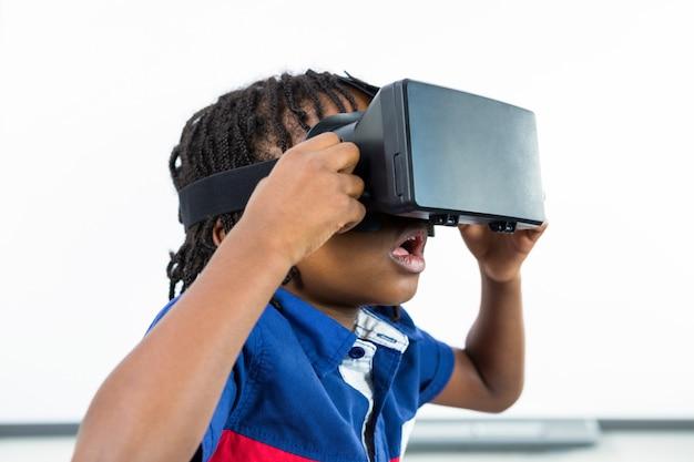 Ragazzo sorpreso che utilizza la cuffia avricolare di realtà virtuale nell'aula