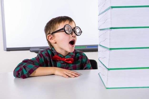 Ragazzo sorpreso dai libri impilati in aula