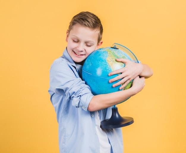 Ragazzo sorridente che abbraccia la mano del globo contro il contesto giallo