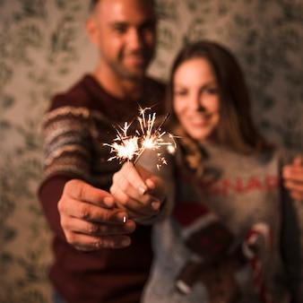 Ragazzo sorridente che abbraccia signora allegra con fiammeggiante luci del bengala