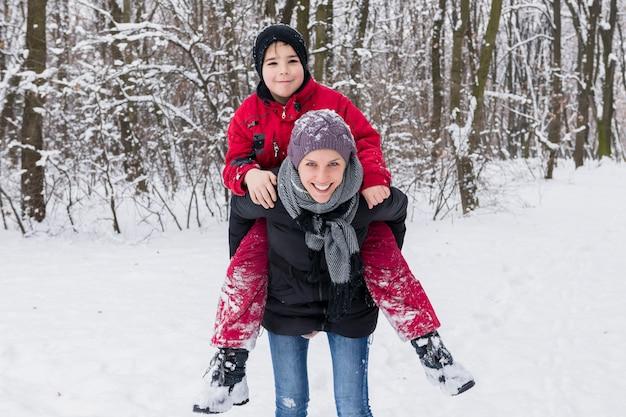 Ragazzo sorridente che gode sulle spalle con sua madre in inverno alla foresta