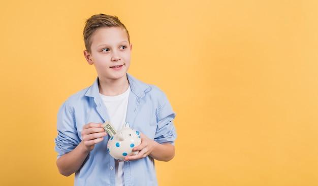 Ragazzo sorridente che inserisce la nota di valuta nel porcellino salvadanaio bianco ceramico