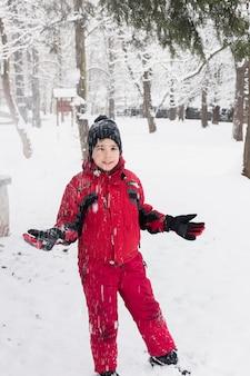 Ragazzo sorridente che sta nel paesaggio nevoso durante le precipitazioni nevose