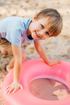Ragazzo sorridente con anello di nuoto sulla sabbia