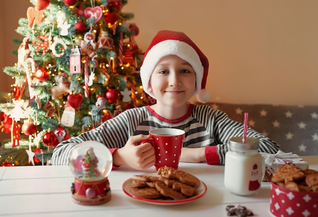Ragazzo sorridente con la tazza rossa di natale di tè all'albero dei christmass. la famiglia con bambini celebra le vacanze invernali. vigilia di natale a casa. ragazzo del bambino nella cucina di natale. ragazzo con cappello santa.