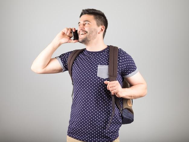 Ragazzo sorridente con lo zaino che parla tramite smartphone mobile