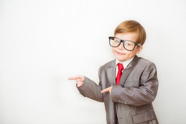 Ragazzo sorridente del bambino che indica il suo dito indice a qualcosa. successo, concetto di business creativo e innovazione