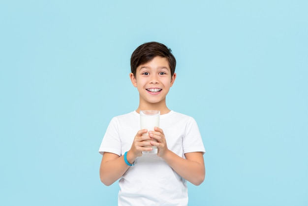 Ragazzo sorridente felice della corsa mista che beve latte fresco isolato sulla parete blu-chiaro
