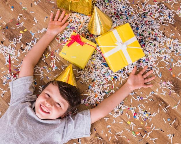 Ragazzo sorridente in cappello di compleanno sdraiato con regali e coriandoli sul pavimento
