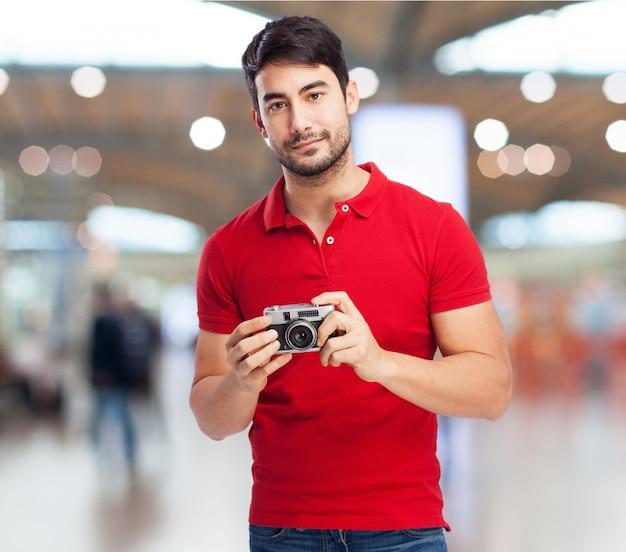 Ragazzo sorridente in posa con la sua macchina fotografica