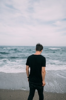 Ragazzo sorridente in una maglietta nera si trova sulla spiaggia sabbiosa.