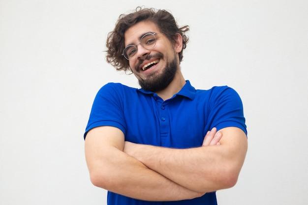 Ragazzo spensierato positivo con le braccia conserte che scrolla le spalle le spalle