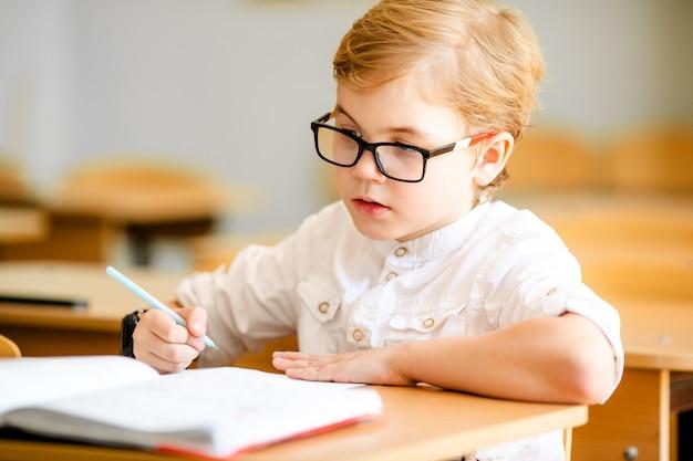 Ragazzo studiando al tavolo su sfondo di classe