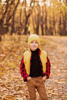 Ragazzo su una protezione gialla che si leva in piedi all'aperto