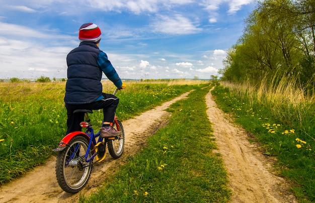 Ragazzo sulla bici sulla strada campestre nel giorno soleggiato