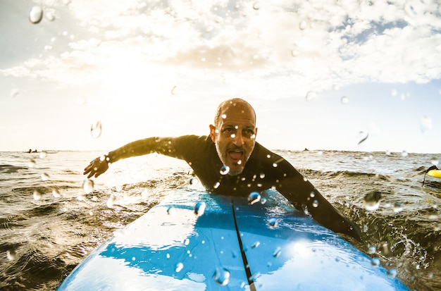 Ragazzo surfista pagaiando con tavola da surf al tramonto a tenerife