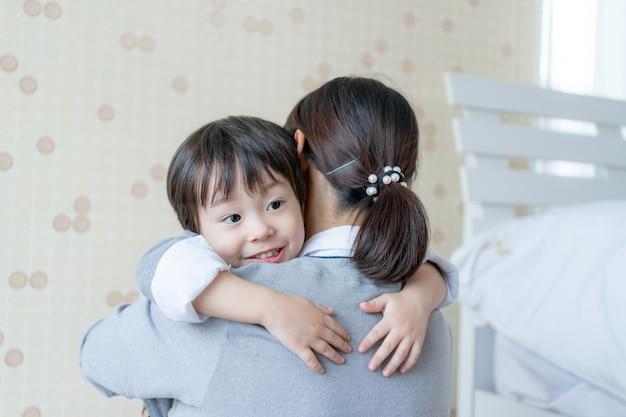 Ragazzo sveglio asiatico che sorride con felicemente e che abbraccia con la madre a casa, spazio della copia, concetto