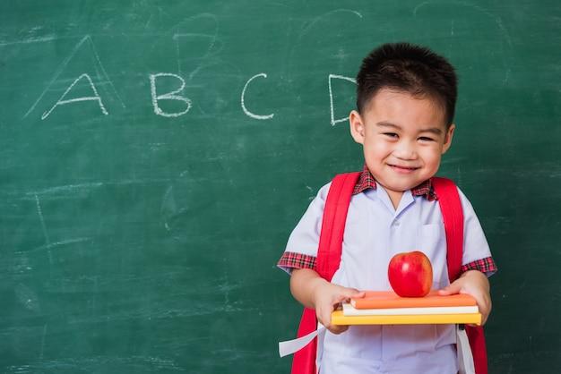 Ragazzo sveglio asiatico felice del piccolo bambino dall'asilo in uniforme dello studente con la mela della tenuta di sorriso della borsa di scuola sui libri sulla lavagna verde della scuola
