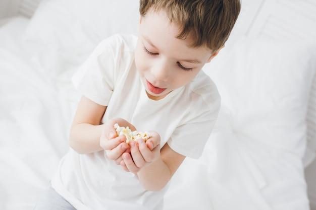 Ragazzo sveglio che mangia popcorn che si siede nel letto con le lenzuola bianche