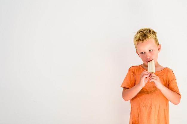 Ragazzo sveglio che mangia un gelato nella priorità bassa bianca