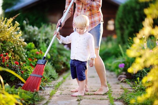Ragazzo sveglio del bambino che aiuta sentiero per pedoni pulito in giardino domestico