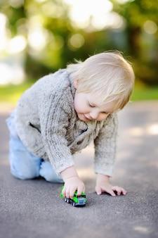 Ragazzo sveglio del bambino che gioca con l'automobile del giocattolo all'aperto al giorno di estate caldo