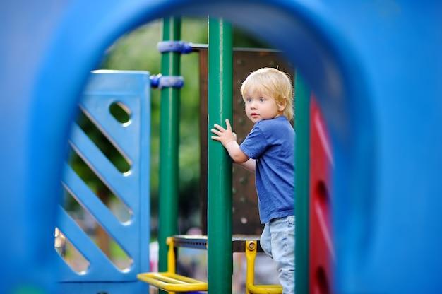 Ragazzo sveglio del bambino divertendosi sul campo da giuoco all'aperto. gioco attivo per bambini piccoli