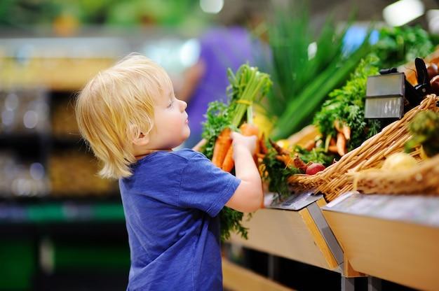 Ragazzo sveglio del bambino in un negozio di alimentari o in un supermercato che sceglie le carote organiche fresche. stile di vita sano per una giovane famiglia con bambini