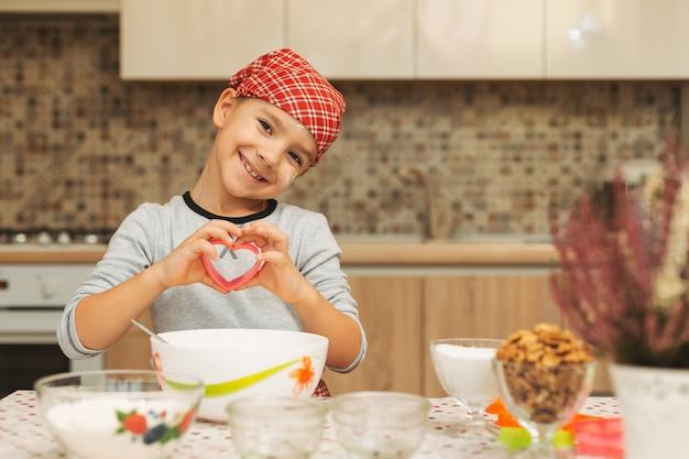 Ragazzo sveglio shef che mostra il suo amore mentre cucina tenendo una forma del cuore per i biscotti