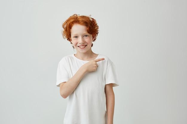Ragazzo sveglio sorridente felice con capelli ricci rossi e le lentiggini che indicano con il dito da parte con l'espressione allegra.
