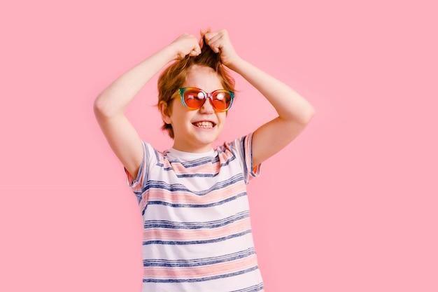 Ragazzo teenager biondo nel sorridere degli occhiali da sole della scintilla