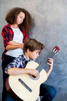 Ragazzo teenager che gioca chitarra acustica mentre ragazza teenager che lo ascolta