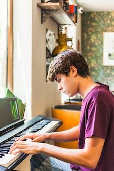 Ragazzo teenager che gioca piano elettrico