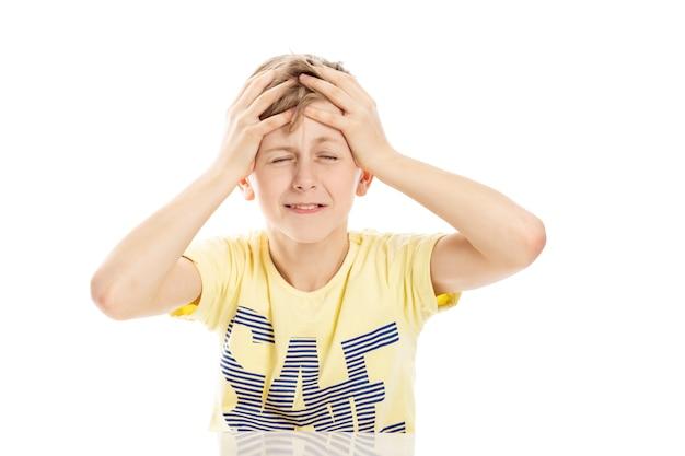Ragazzo teenager che grida con rabbia mentre seduto al tavolo. isolato su sfondo bianco.