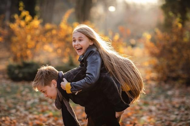 Ragazzo teenager sveglio e ragazza che giocano insieme nel parco di autunno. copia spazio.