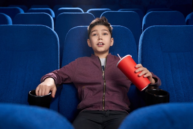 Ragazzo teso che guarda film horror nel cinema