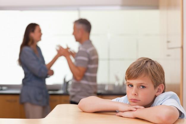 Ragazzo triste che sente i suoi genitori avere discussione