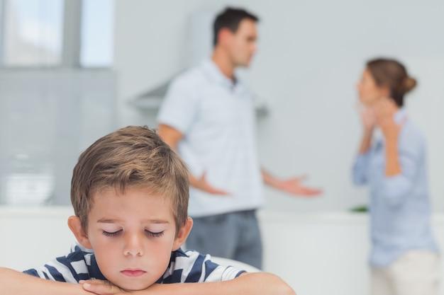 Ragazzo triste mentre i genitori litigano