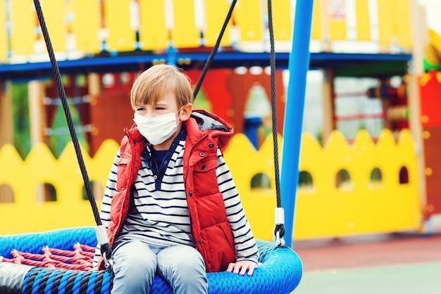 Ragazzo triste nella maschera di protezione che gioca all'aperto. bambino annoiato al parco giochi vuoto fuori. quarantena per il coronavirus.