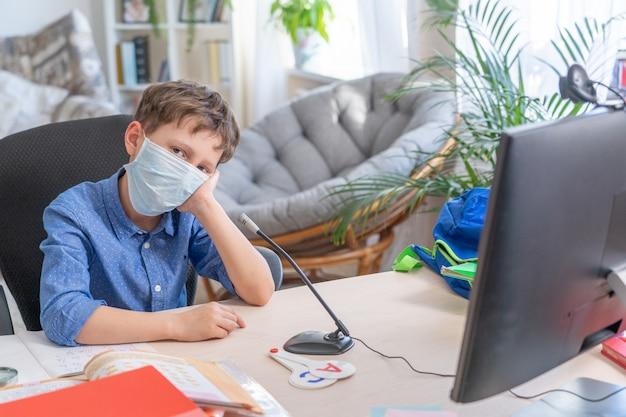 Ragazzo triste nella maschera facciale utilizzando il computer facendo i compiti durante la quarantena di coronavirus