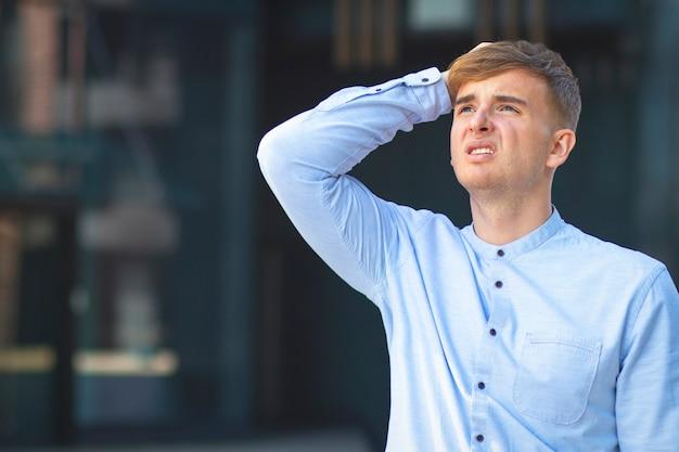 Ragazzo vestito formalmente con una camicia bianca. mal di testa o febbre in un uomo.