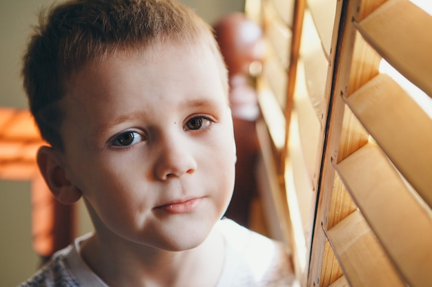 Ragazzo vicino alla finestra. bambino che guarda fuori. concetto di stile di vita, vacanze